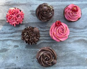 strawberry and choc cupcakes on table